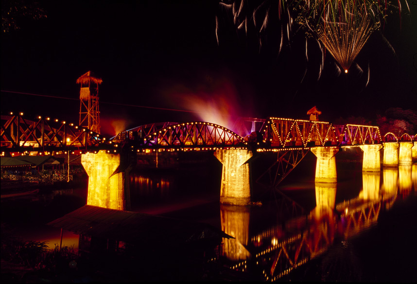 You see a fully illuminated bridge during Loy Krathong.