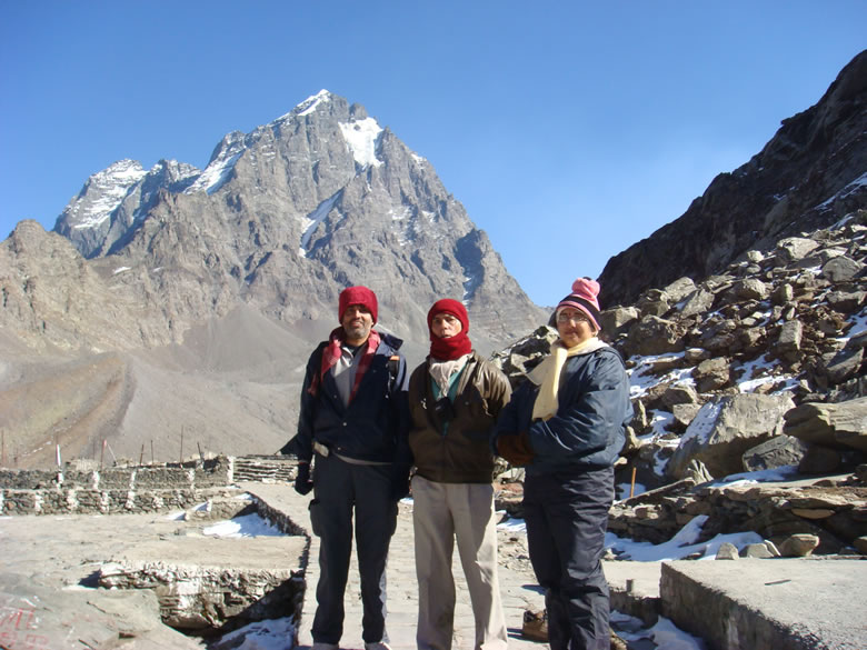 You see us with the Mani Mahesh Kailash in the background. A rock formation in the shape of a ``Shivling`` on Kailash is considered to be the manifestation of Lord Shiva. The local people call the snowfield at the base of mountain Shiva``s Chaugan.