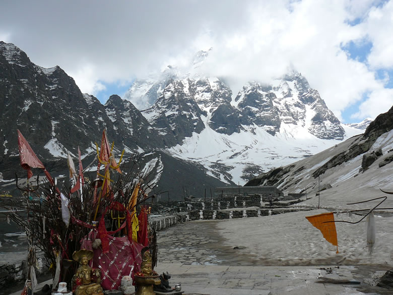 A view of the Manimahesh temple with lake on the left and snow covered mountains in the background.