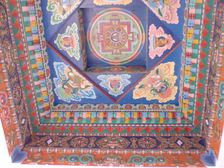 Colourful ceiling of the traditional entrance way to Batseri village, with an elaborate painted Buddhist mandala.