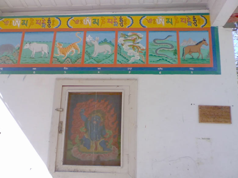 Half Buddhist zodiac painted on either wall of the entranceway, along with a painting of tantric deity, Vairochana Padmasambhava, on this one.