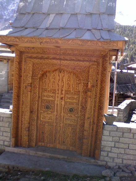 Intricately carved door of a typical little temple shrine.