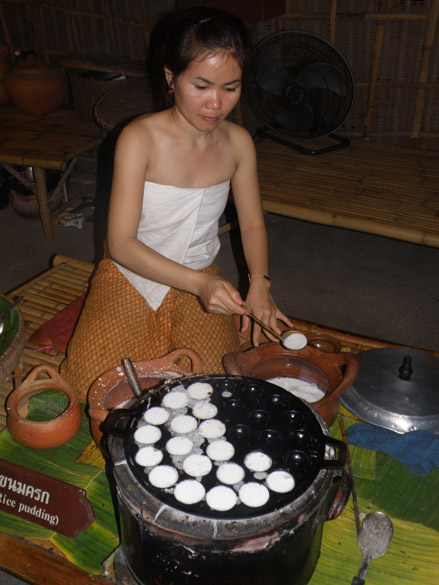 A Thai girl makes rice pudding and serves it hot. The show takes place in a huge auditorium that can seat 2000 people.