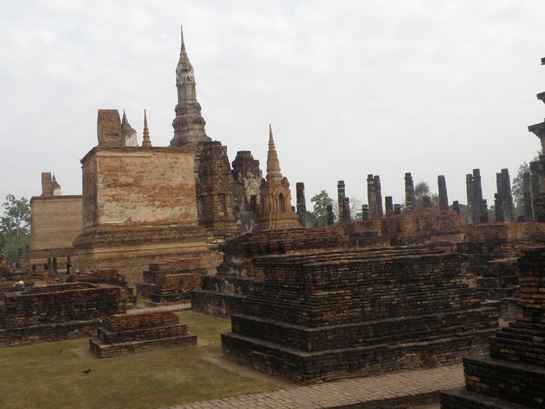 You can enter Wat Mahathat from the main entrance. This picture gives you an overview of the monument. On the right is the huge Buddha whose pictures you saw earlier. In the left are two standing Buddhas in a brick wall structure. In the centre is large lotus bud chedi that holds a Buddha relic. The lotus chedi rises above what`s left of its pillars and presides over several magnificient Buddhas and hundreds of chedis.