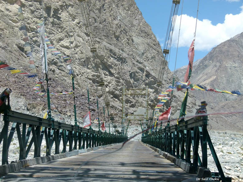 Suspension Bridge.... protected by struts and Buddhist prayer flags. The Balti people are culturally and racially different from Ladakh – are believed to be of Greek descent, retaining fair skin with blonde and curvy hair. Some anthropologists believe they are descendents of King Alexandar's army.
