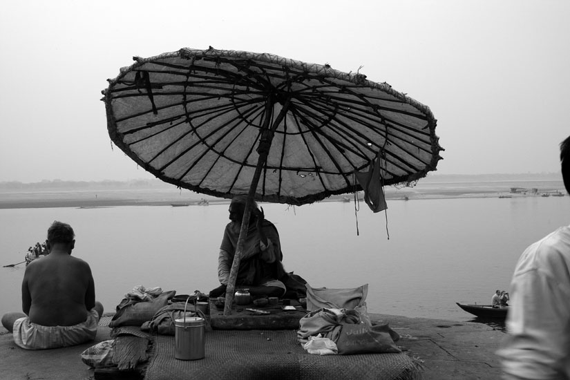A hermit sitting on the ghats to help people perform rituals for the deceased ones.