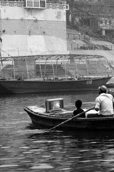 Technolgy and Marketing at it peak- A boat owner with a TV and battery on his boat to show and sell people the recordings of prayers.