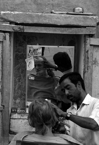 A barber shaving a foreigner on the ghats of Varanasi.