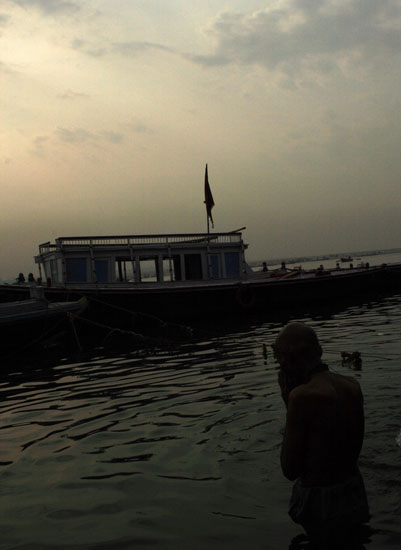 An old man offereing prayers while bathing in River Ganga.