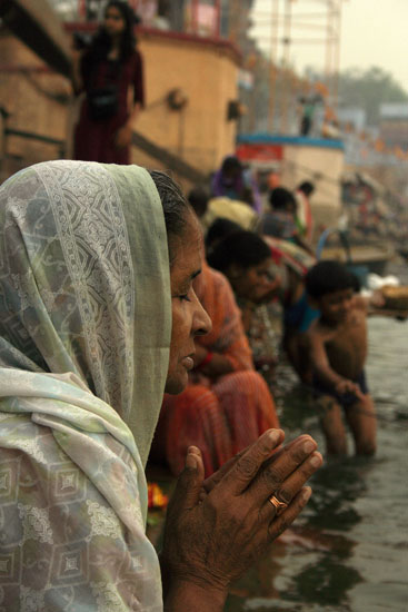 An old lady performing prayers for her deceased ones.
