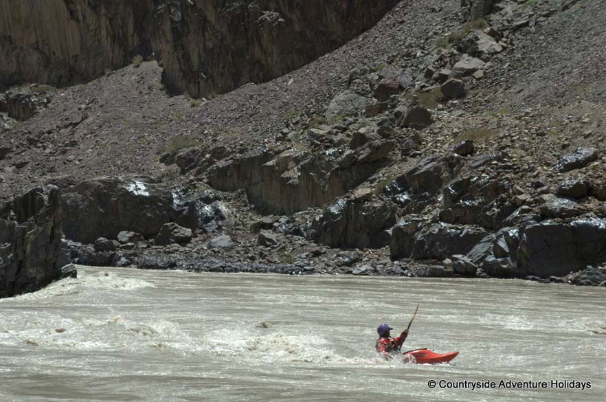 The kayaker is also practicing. `Zanskar River originates from the high altitude plateau of Sarchu on the border of Himachal Pradesh and Jammu and Kashmir . Originally known as the Tsarap the river gorges a path out of the rocky mountains of western Himalayas , dropping in a continuous torrent of class V rapids. The river then eases into the forbidden Kingdom of Zanskar and slowly flows past the capital at Padum. Here it joins with the Stod river which flows down from the Pensi La pass on the road from Kargil to Padum`.