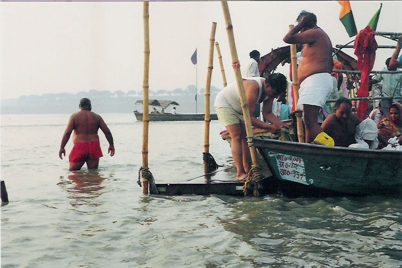 You see devotees getting ready to take a dip at the Holy Sangam. Up to a point the water is deep then it gets very shallow on the Ganga side. Shallow enough to walk through. The Government has made parking spots from where devotees can get into the water with the support of bamboos. My wife and I had half a dupki ie dip in the Sangam.