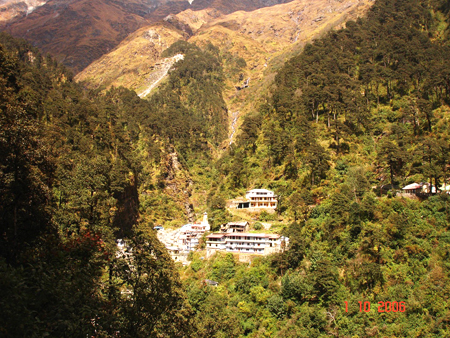 An overview of the shrine with the hill behind. Close to the Yamunotri is a stream that comes in the center of the mountain in this picture. It comes from the top of the mountain & is one of the sources of the Yamuna river. The source of the river is Band