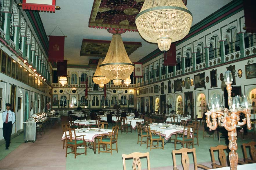 You see a Durbar Hall (built by Maharana Fateh Prakash). It is decorated with portraits of Maharana dynasty. Arms are displayed on the walls. You see an overview of the hall. See the chandeliers. See the red carpet on the ceiling. Next picture has its close up.