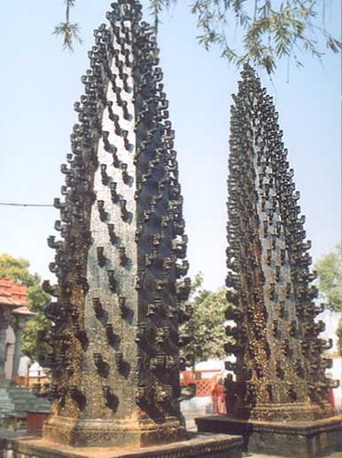 The two large columns that you see are situated in the courtyard of the temple and called Deepswthambs or lamps. They are symbols of Maratha architecture. The lower part of the swthamb is very oily. We saw a similar swthamb in Mumbai recently. Instead of being lit by oil there were bulbs.