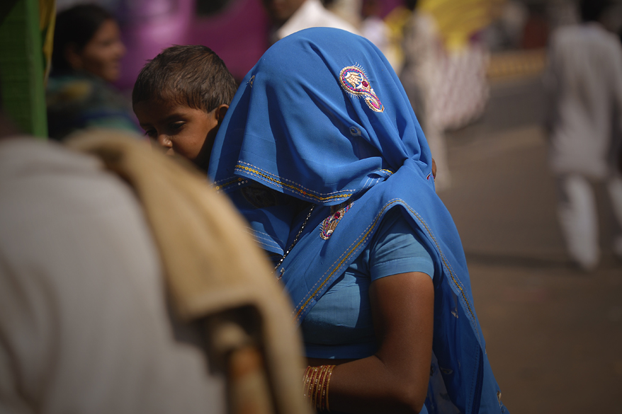 "<font color=""#f0d5a6"">Woman, India</font> <br />Draped in blue, a woman is waiting for the bus near Marwar in India. The most common style is for the sari to be wrapped around the waist, with one end then draped over the shoulder.