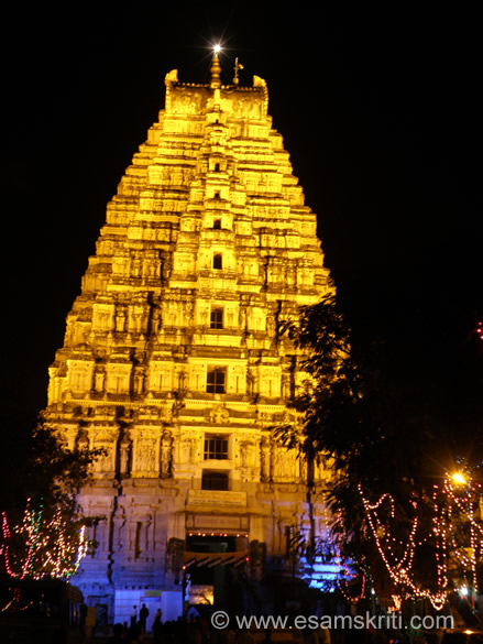 The festival was held on 27-29 January 2011 and is organised by Karnataka Tourism. The celebrations include classical dance and music shows, animal parades, light and sound shows. Most importantly the city and monuments are lit up. This section shows you key monuments by day and night. You see the giant tower (Gopuram) of the Virupaksha temple. It is a temple dedicated to Lord Shiva and considered the most sacred temple in Hampi.