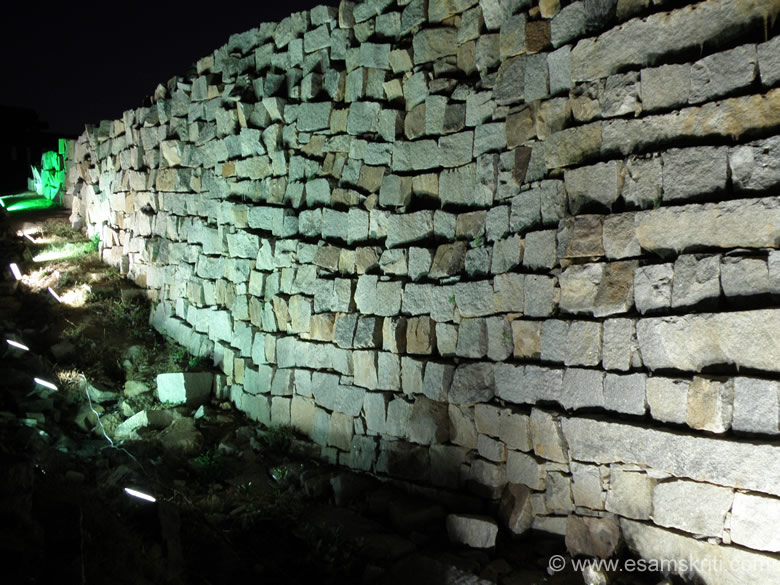 The road from the Hampi market to Krishna Temple has the Hemakuta Hill on its right. This stone wall divides the two. You see them lit up.