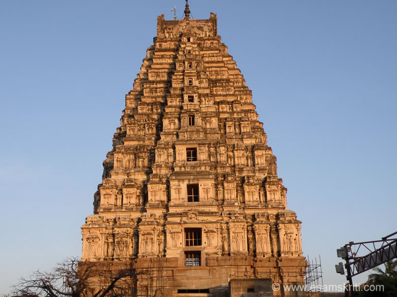 You see the east facing gopuram of Virupaksha temple sunset time. It is a 52m high.  Te lower two tiers is made of decorated stone work, thereafter with bricksuperstructure. Proluganti Tippa, a commander of Devaraya II (1422-46) built the gopuram. The temple complex assumed its present shape around 1520. Today the temple overlooks by the long and broad Hampi bazaar lined with remains of ancient mandapas.