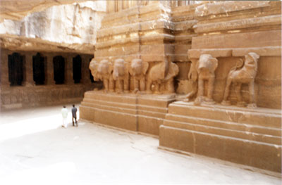 A picture of the plinth on which stand the main temple + vimana. All around the podium, we notice a row of elephants and rampant lions bracketed by a series of deeply carved moldings both from above and below that produce an aura of majesty of massive plinth for monolith edifice. Note that elephant trunks are chopped off.