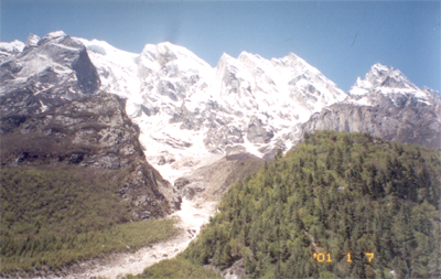 Bhagirathi Peaks in front with a stream in the center. In between somewhere is a trekking path.