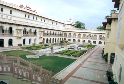 Welcome to the Rambaugh Palace Hotel. Spread over 47 acres it was built in 1835 as a hunting lodge. It got converted into a palace in 1925 when Maharaja Sawai Mansingh II moved in. Converted into a hotel since 1957 India's premier hotel chain, Taj Hotels, have been running it since 1972. A part of the Palace continues to be the residence of the Maharaja of Jaipur/family. What you see is the palace courtyard.