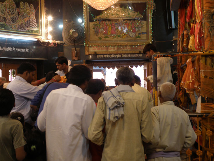 Inside the temple you see devotees worshipping Lord Krishna.