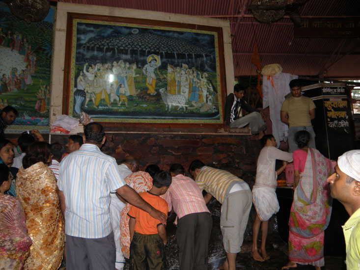 A particular point of the mountain is considered sacred where devotees do Abhishek ie what you see devotees doing.