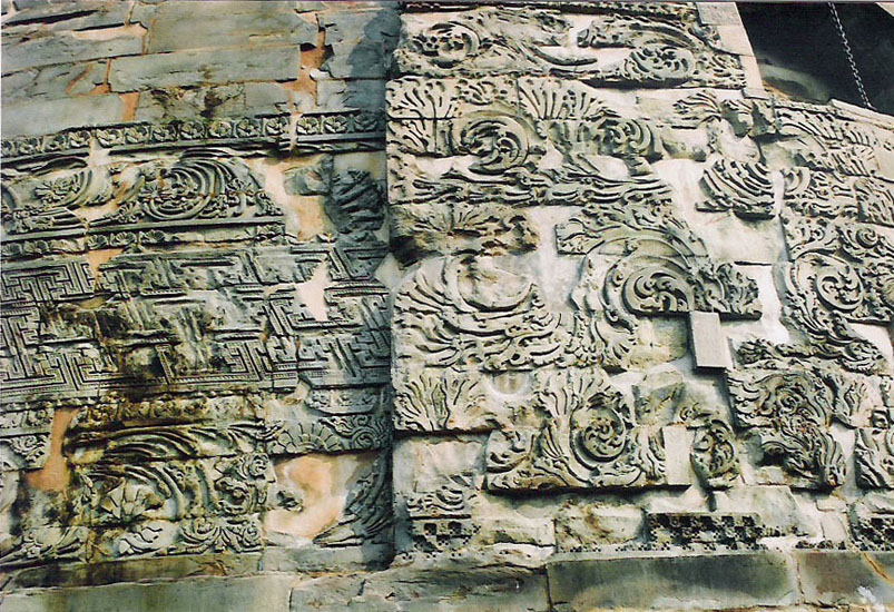 As mentioned above the lower portion of the stupa has a broad course of beautifully carved stones having geometrical designs, swastika, leaf and floral patterns with birds and human figures. That is what you see.