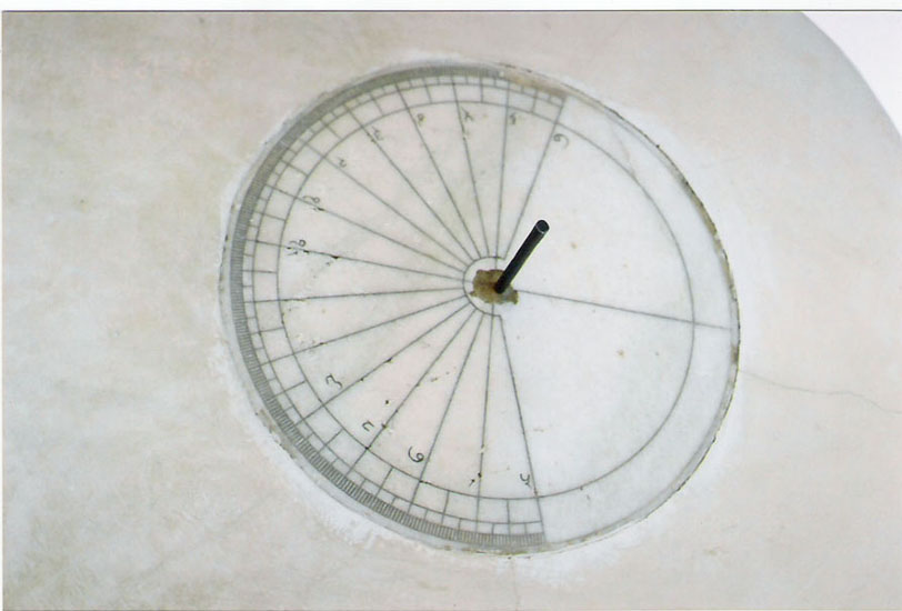 Transit Instrument: this instrument is built in the plane of the meridian circle (the circle joining north, south and zenith point). It is used for observing the zenith distance of any celestial body (corresponding to its mid-day). There are two pegs at the top of the instrument fixed with string in the center of graduated quadrants. When the object is in the south of the prime vertical (the circle joining east, west and zenith point), the southern peg is to be used, otherwise the northern peg is to be used. At the time of the transit of the celestial body, the observer has to keep his eye on the string and move it forward or backward to determine the particular position of the string at which the center of the heavenly body could be seen, through the point of intersection of peg and wall. The reading of the quadrant at the position of the string gives the zenith distance. After 12.26 no use since Sun crosses the instrument.