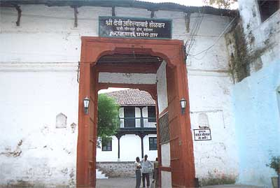 Entrance to Shri Devi Ahilyabai Holkar's Wada palace built in 1766. Rajgaddi and Rajwada: A life-size statue of Rani Ahilyabai sits on a throne in the Rajgaddi within the fort complex. This is the right place to begin a tour of Maheshwar, for this pious and wise queen was the architect of its revived importance. Other fascinating relics and heirlooms of the Holkar dynasty can be seen in the other rooms, which are open to the public.