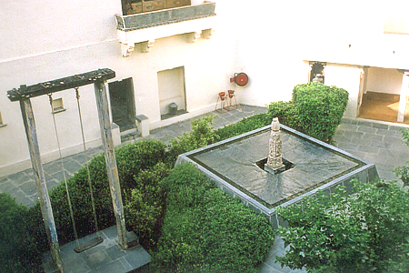 What you see is the Janana Courtyard (used by ladies). On the right is a fountain with the excavated stone from the 8<sup>th</sup> century old Jain temple in the village. On the left is an 18<sup>th</sup> century old swing that was used by the queens of earlier times. In the center is the back side of the Lotus Courtyard.