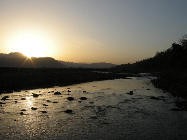The sun raises its head as quiet flows the Ramganga through the heart of Jim Corbett.j