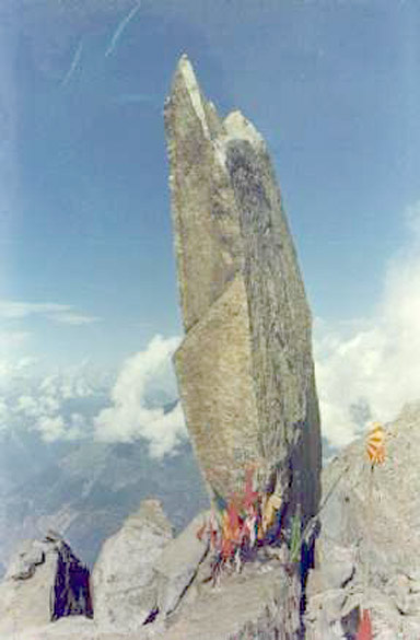 "This is from a postcard of Shikhar Shivling, a place of pilgrimage at the top of Kinnaur Kailas. Only intrepid young trekkers/mountaineers can attain that great height involving parts of sheer vertical ascent, often in the midst of light snowfall. It is accessible only for a fortnight around the Shravan Purnima every year, being utterly out of bounds rest of the time. A young temple priest from another place in HP revealed that there was a rock formation there resembling the Nandi bull, Shiva's mount. Most Himachulis are devout people, and as a mountaineer guide narrated, ""Yahan ke chappe-chappe mein Shivji ka vaas hai."" And they also revere the rough, unpolished High Himalayan clear quartz found in parts of the HP highlands, placed in practically every shrine at home or in the temples as a symbol of Shiva."