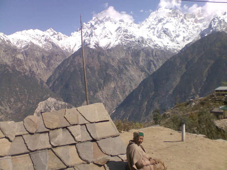 Elderly woman enjoying warmth of the Sun outside her dwelling. Most Himalayan mountain folk, young or old, are nimble-footed like the proverbial mountain goats, traversing miles up and down rough stone-and-earth tracks, often with heavy head loads, in the course of a single workday. There is no option either, homes often being hewn into the cliff sides up dizzy heights, naturally adding to the beauty of ecological habitat with low environmental impact. Some of the better-off youthful families I visited, each had even three dwellings conveniently located for different seasons – one in the high mountains in winter, often constructed of pinewood, also with secure cattle sheds, also with a school in the vicinity; another one in the middle of terraced fields through the wet agricultural season – to harvest time, and the third one lower down by the roadside, for convenient marketing of farm and horticultural produce.