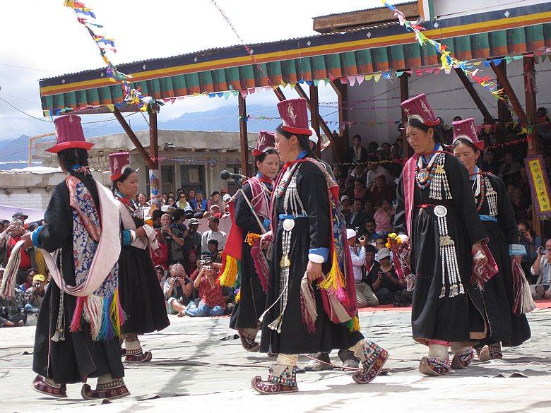 This dance is the MANTOK STANMO from the Nubra Region of Ladakh. Women with red head-dress in silk and brown robes with mojri like footwear.