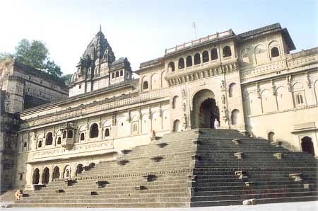 A closer view of the fort entrance from the ghat side. The ramparts of the fort were built in the 16th century, by Mughal king Akbar; Maheshwar itself has been continually inhabited for some 4000 years. Today, Maheshwar is also known for its distinctive hand-woven saris called Maheshwari. Peshwa Ghat, Fanase Ghat and Ahilya Ghat line the river Narmada, flights of steps lead down from the sandy banks to the river and through the day a kaleidoscope of rural India can be seen here, in the pilgrims and holy men who sit here in silent meditation; in the rows of graceful women, who carry gleaming brass pots down to the holy, life giving river; in the ferry loads of villagers who cross and recross these surging waters.