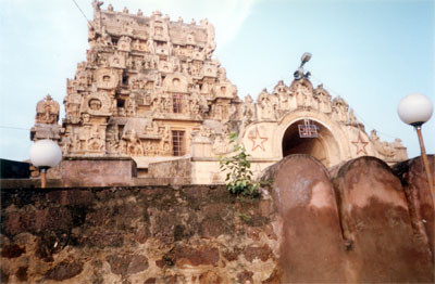 Here you can see that that the welcome arch & the gopuram are two different structures. The gopuram is 90 feet high and abounds in sculptural beauty, as you shall see later. The glory of the king s successful invasions & charitable acts have been inscribed on stone. You can also see a wall that looks like a fort wall. As you shall see later the eastern side has a fort wall.