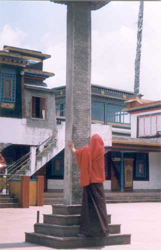 Head shielded from the sun, a lone monk reads the inscriptions on an 18-foot tall stupa in the courtyard of Rumtek monastery.
