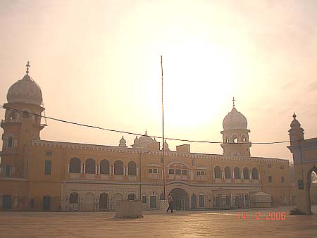 This is the Nishan Sahib against the rising sun. This is the main entrance gate of Nankana Sahib. The sardar you see is from gurdaspur.