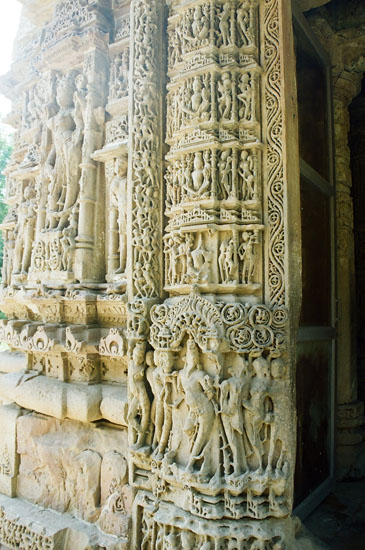 The exterior wall of the Mandapa is relieved by niches containing images of the twelve Adityas, Sikpalas, Goddesses and Apsaras. The exterior of the sanctum has many carved images of the Sun God, portrayed as wearing a belt and long shoes as in the Dakshinaarka temple at Gaya. You see carvings at temple entrance.