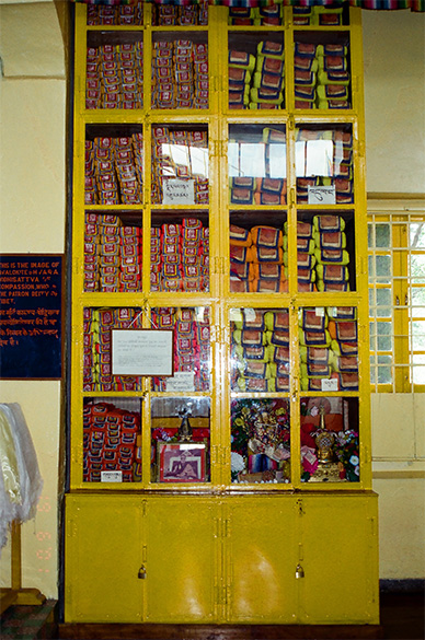 This cupboard has a collection of texts called Kagyur, translations of the actual teachings of Buddha. These 100 volumes translated from Sanskrit are the authentic teachings of Buddha himself and contain the whole collection of sutras and tantras.