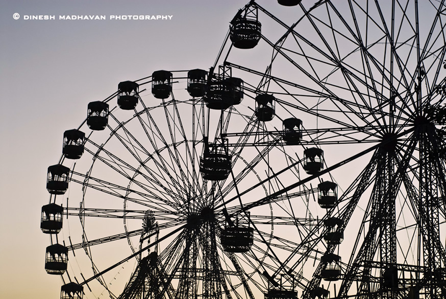 The giant wheel  at the mela silhouetted agianst the sky.