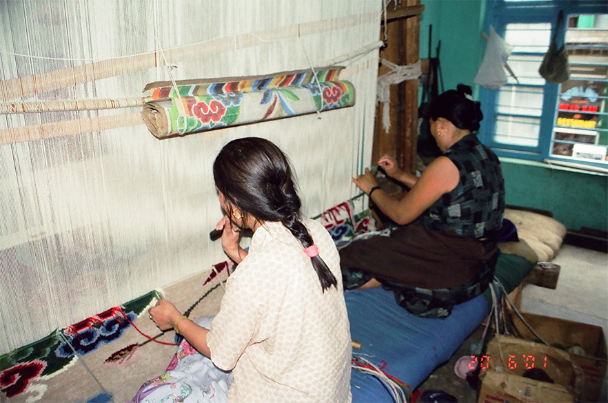 Tibetan women weaving carpets inside a Cooperative.