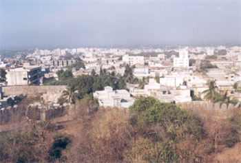 Overview of Junagarh city from Uparkot fort. It is an ancient city that lies at the foot of the Girnar Hill and takes its name from the `Old For` which circles the town. The Girnar Hill stands from 2500 B.C. having a story of its own. The antiquities of Junagarh go back to the times of Emperor Ashok 250 B.C. whose 14 Rock Edicts can be seen cut into a great rock outside the city - you shall see its picture later.