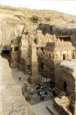 Overview of Temple from northwest side. It stands within a rectangular court that measures 300 feet by 200 feet. It consists of a Vimana (dome like structure at the far end) in its sanctum cell is where Lord Shiv is enshrined as a Linga. Mandapa 1 (main temple) the two occupying an area of app 150 feet (behind the free standing column) consists of a huge pillared hall on top of which are four lions., Mandapa 2 has housed Nandi the carrier of Lord Shiv (next to the free standing column) and double storied entrance (extreme right of picture). The vimana + main temple are on a plinth that has elephants and dhwajasthambhas (columns) on either side. The temple is designed like a chariot.