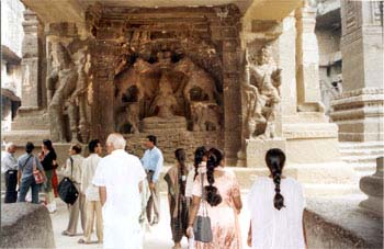 Now we come to ground level. Temple entrance has in the center Goddess of Wealth, Gajalakshmi seated on a full-bloomed lotus in the midst of a lotus pond while elephants above pour water by way of ritual adoration abhishek as we in India call it.