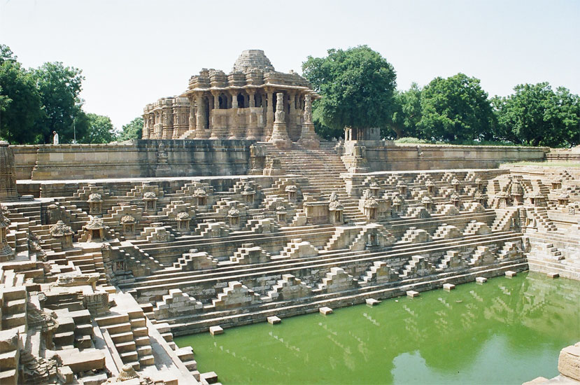 About 100 kms from Amdavad say 1.5 hours drive is the Sun Temple Modhera. It was probably constructed during the reign of  King Bhimdev I (1022-1063 A.D.) as it is notified by the inscribed slab in the sanctum wall which reads 'Vikram Samvat' 1082 i.e. 1025-1026 a.d. Interesting it was during the same period that the Dilwara  temples at Mount Abu were constructed by Vimal Shah and the grand Brihadesvara temple at Thanjavur in South India. The whole complex is set in a rather well maintained garden almost a park. The temple marks the greatest achievement of the Solanki style. Standing on a raised terrace (plinth), this temple consists of three separate elements axially aligned and integrated in a balanced architectural composition. These comprise 1) the Main Temple complex including sanctum with ambulatory, Kapili, closed Mandapa with lateral transepts and porch, 2) A detached Sabhamandapa with a Torana in front and 3) a large flagged tank decorated with numerous miniature shrines. What you see is the tank Ram Kund; one is Sabhamandapa and behind is the main temple.