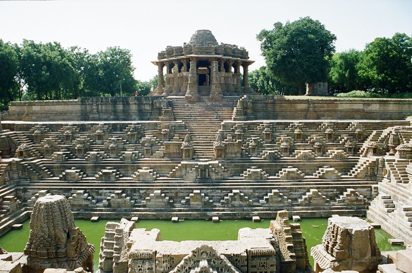 A front view of the complex, Ram Kund in front with temple complex behind. Note the steps that go up to the sabhamandapa and two columns right in front of the temple a close up of which you will see in the next picture. The temples right in front picture are damaged without their mandapas. The temple at Modhera is the most important of all sun-temples built in the whole of Gujarat.  It enjoys the same significance as other two well known sun-temples in Kashmir (Martand) and Orissa (Konark).  The remains of this magnificent architectural monument still reflect the glimpses of elegance and testify the sanctity of the site.